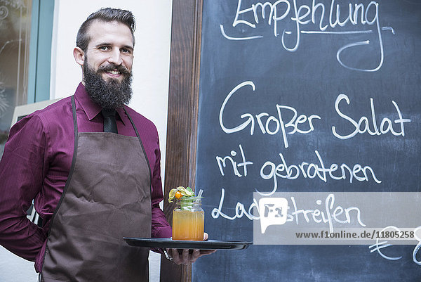 Close-up of young man standing by chalkboard menu with tray of mocktail