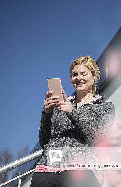 Woman in checking her smart phone during exercising