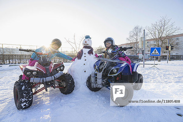 Girls riding quad bike and leaning on snowman