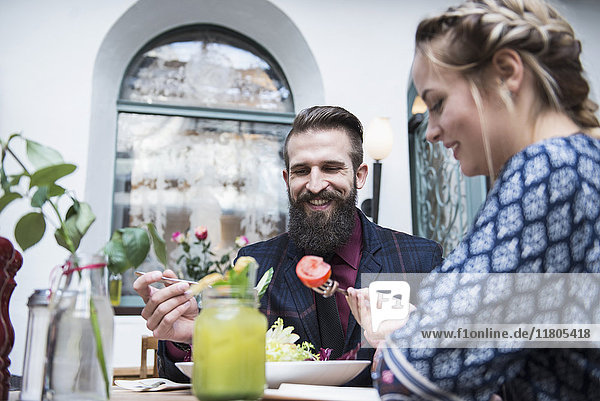 Young couple eating salad at restaurant