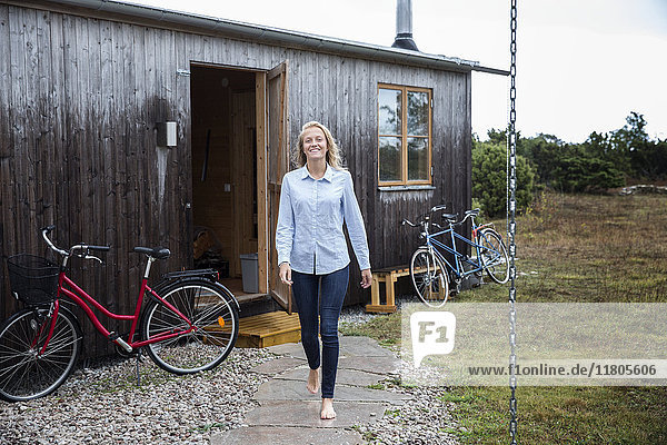 Smiling woman in front of wooden house