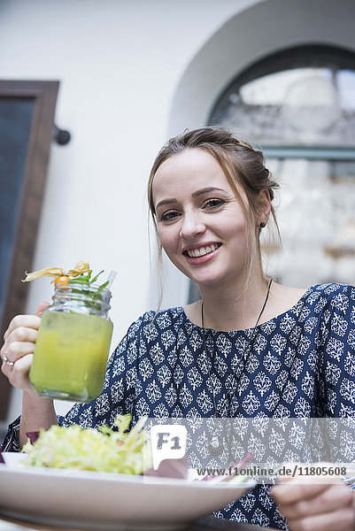Portrait of young woman holding mocktail in jar glass by salad bowl