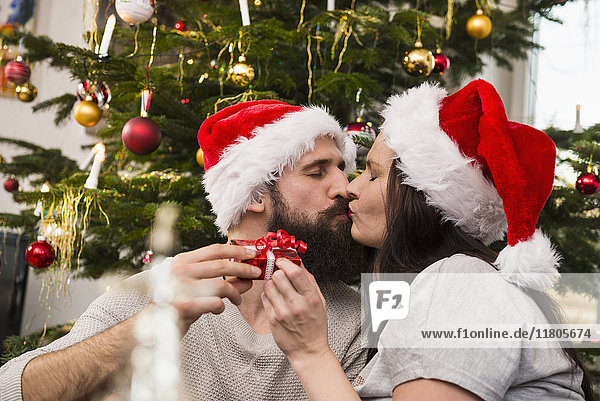 Couple exchanging gifts and kissing