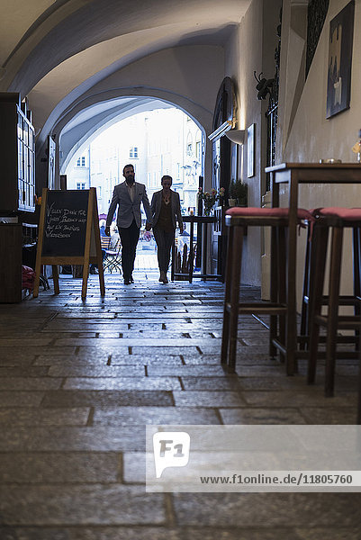 Young couple holding hands and walking at sidewalk café