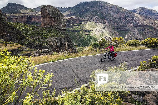 Mountain biker riding electric bicycle on mountain road
