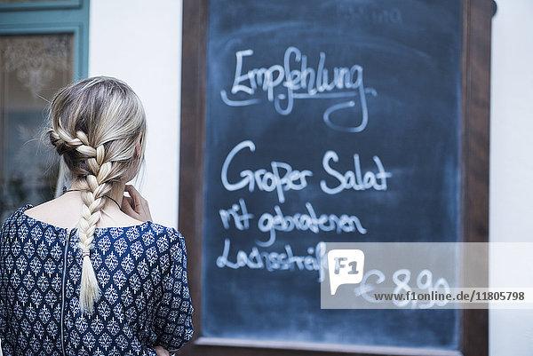 Rear view of young woman reading chalkboard menu