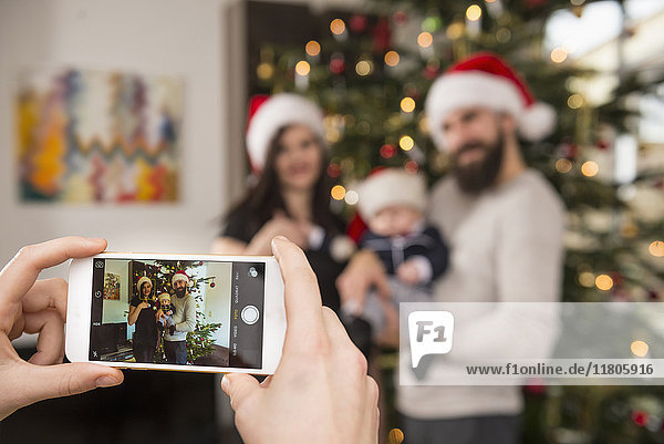 Woman photographing family using phone