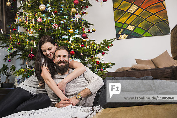 Couple embracing against Christmas tree at home