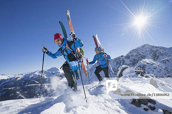 Skiers walking downwards on mountain slope