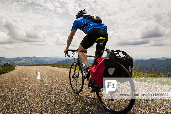 Rear view of man riding bicycle on road