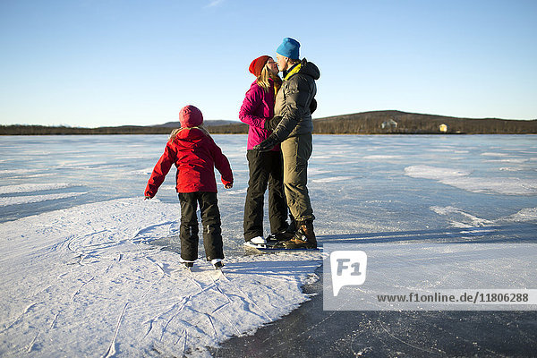Parents with daughter skating on frozen lake