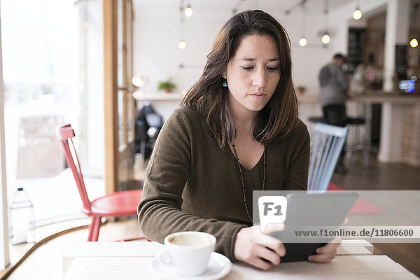Woman using digital tablet in cafe