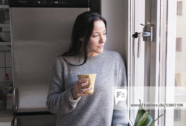 Woman holding mug  looking through window