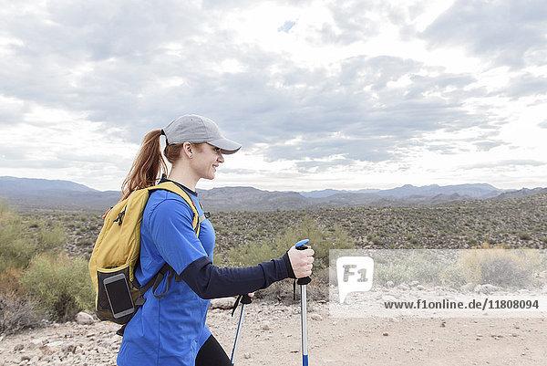 Caucasian woman hiking on rocky path in desert
