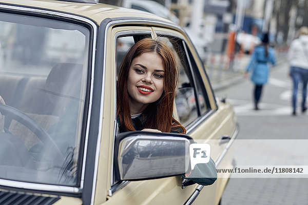 Smiling Caucasian woman leaning on door driving car