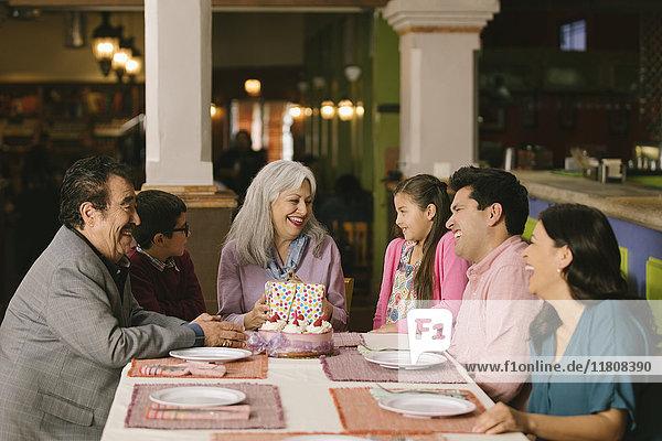 Family celebrating birthday of older woman in restaurant
