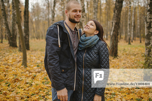 Middle Eastern couple standing in park in autumn