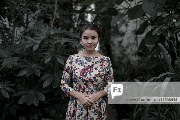 Asian woman smiling near foliage