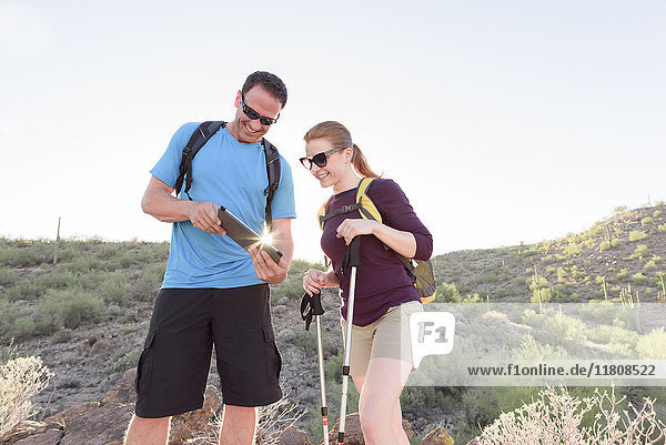 Couple using digital tablet while hiking