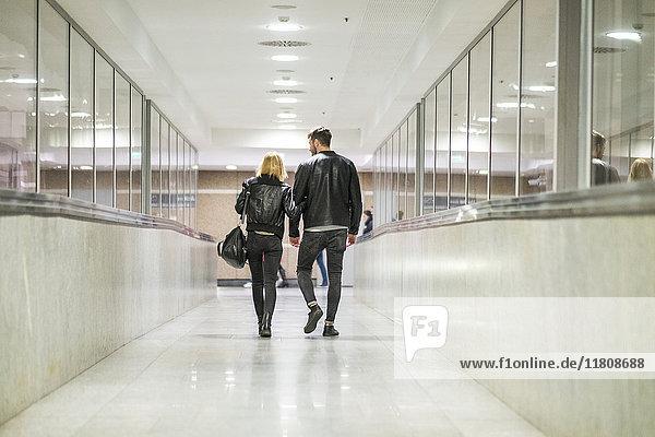 Rear view of Caucasian couple walking in corridor