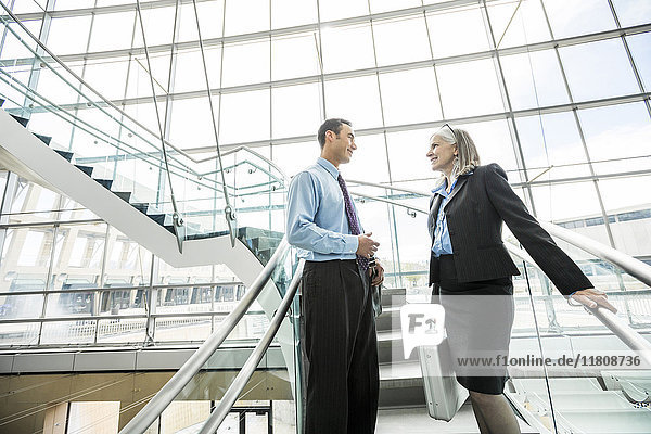 Business people standing on staircase and talking