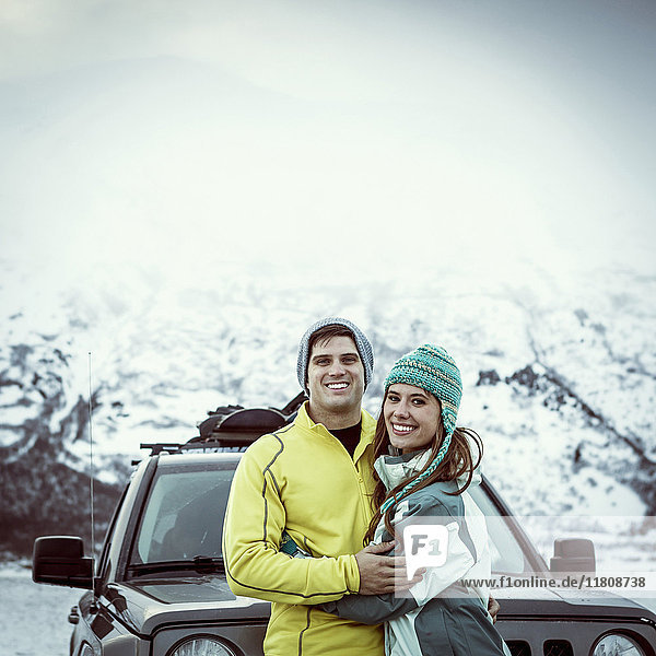 Caucasian couple hugging near car in winter