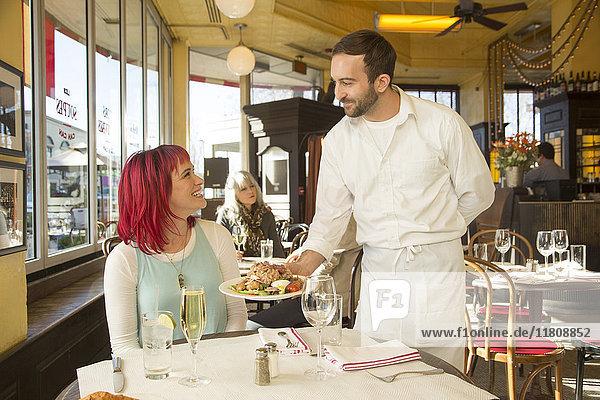 Caucasian waiter serving plate to customer