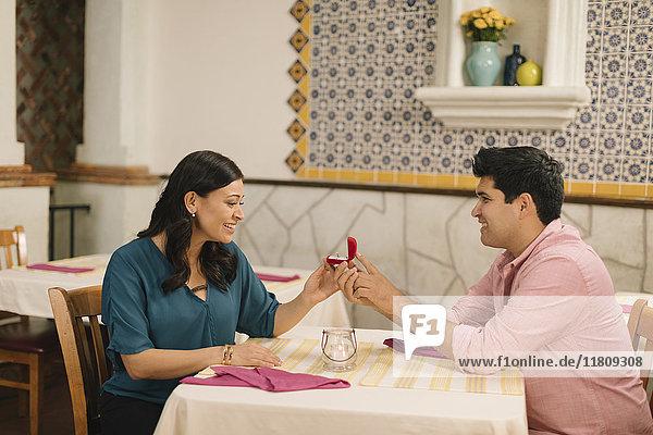 Hispanic man proposing marriage to woman in restaurant