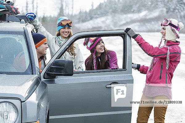 Friends laughing near car in winter