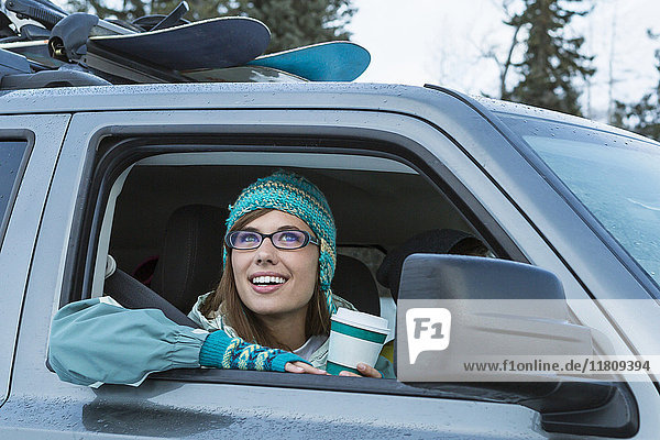 Caucasian woman leaning in car window in winter