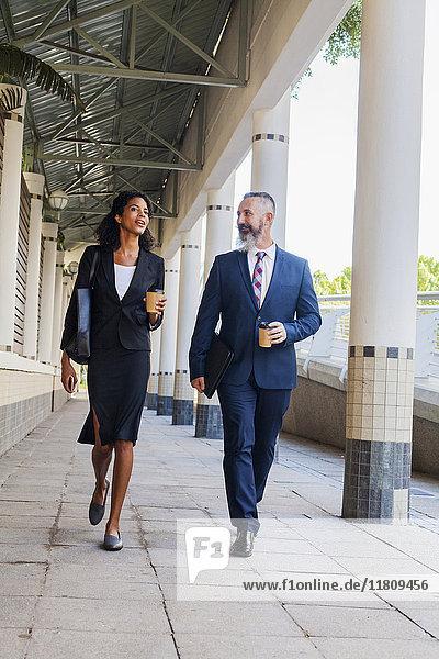 Business people walking on sidewalk