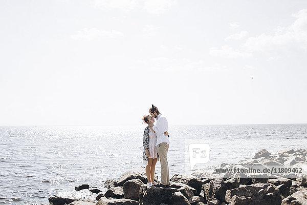 Nahöstliches Paar umarmt sich auf Felsen in der Nähe des Meeres