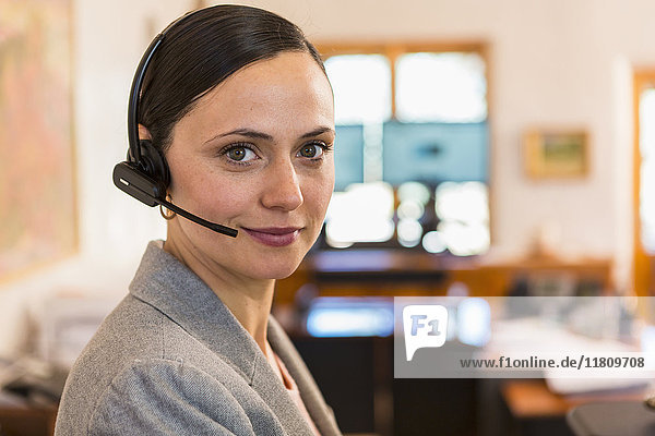 Portrait of smiling Caucasian businesswoman wearing headset