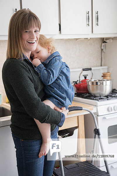 Caucasian mother holding daughter sucking thumb in kitchen