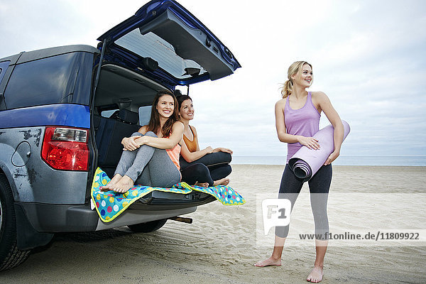 Smiling Caucasian women on beach with car