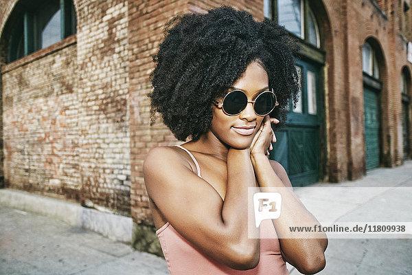 Black woman near corner of brick building