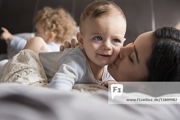 Caucasian mother laying on bed kissing baby son