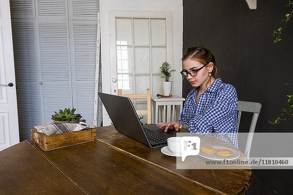 Caucasian woman sitting at table using laptop