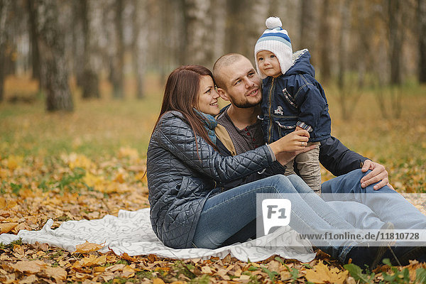 Middle Eastern couple sitting in park with baby son in autumn