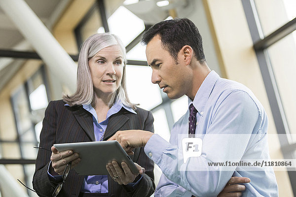 Curious business people using digital tablet