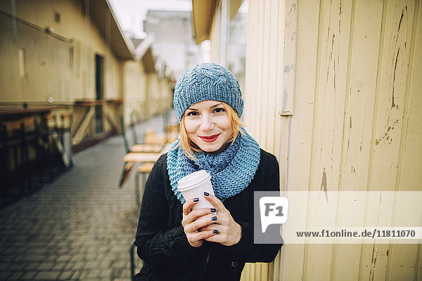 Portrait of smiling Caucasian woman holding coffee cup