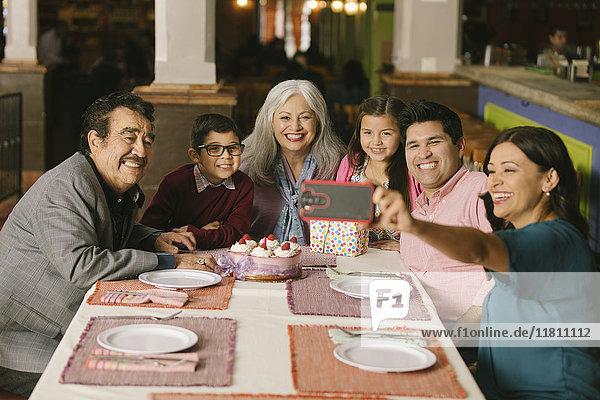 Family celebrating birthday posing for selfie in restaurant