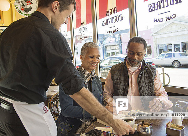 Waiter serving coffee to older couple in coffee shop
