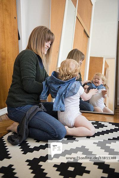 Reflection in mirror of Caucasian mother and daughter kneeling on floor