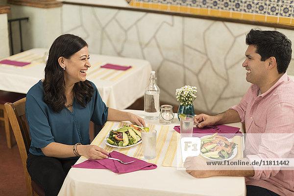 Hispanic couple laughing in restaurant