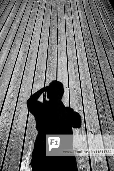 Shadow of Caucasian man with camera on wooden floor