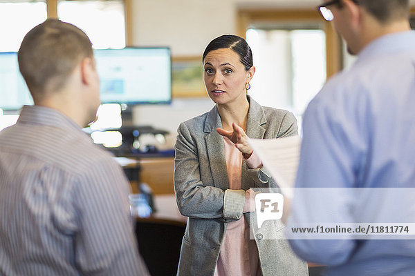 Businesswoman gesturing and talking to businessmen in office