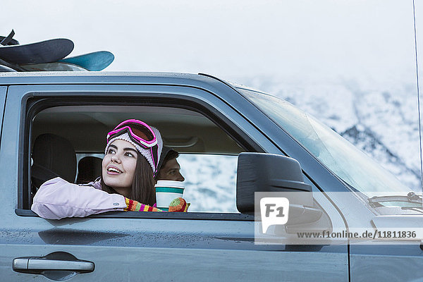 Mixed Race woman leaning on car window in winter