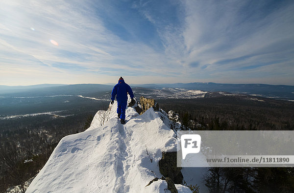 Caucasian man hiking on mountain top in winter