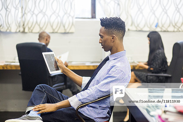 Black man using digital tablet in office